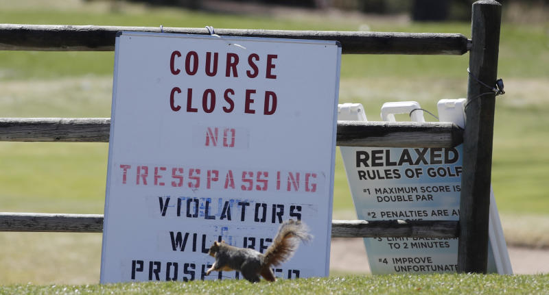A squirrel runs past the sign outside Harvard Gulch Municipal Golf Course after it, along with other city-owned courses and parks, were closed until Friday, April 10, to group activities in an effort to reduce the spread of the new coronavirus Tuesday, March 24, 2020, in Denver. According to the World Health Organization, most people recover in about three to six weeks depending on the severity of the COVID-19 illness. (AP Photo/David Zalubowski)