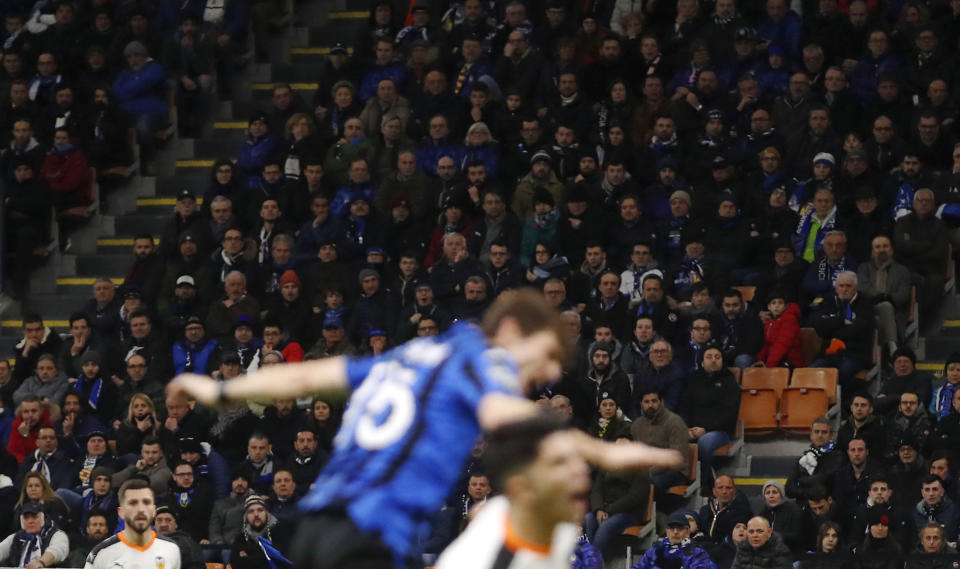 FILE - In this Wednesday, Feb. 19, 2020 file photo, spectators sit in the stands during the Champions League round of 16, first leg, soccer match between Atalanta and Valencia at the San Siro stadium in Milan, Italy.