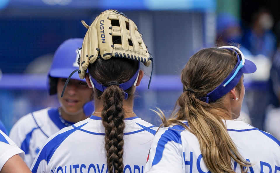 Italy's Giulia Koutsoyanopulos puts her glove on her head during a break in the softball game between Italy and the United States at the 2020 Summer Olympics, Wednesday, July 21, 2021, in Fukushima , Japan. (AP Photo/Jae C. Hong)
