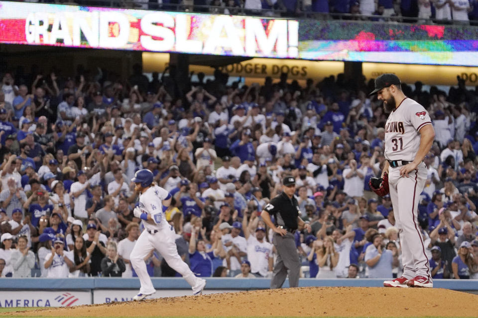 Los Angeles Dodgers' Justin Turner, left, rounds third after hitting a grand slam as Arizona Diamondbacks starting pitcher Caleb Smith stands on the mound during the second inning of a baseball game Saturday, July 10, 2021, in Los Angeles. (AP Photo/Mark J. Terrill)