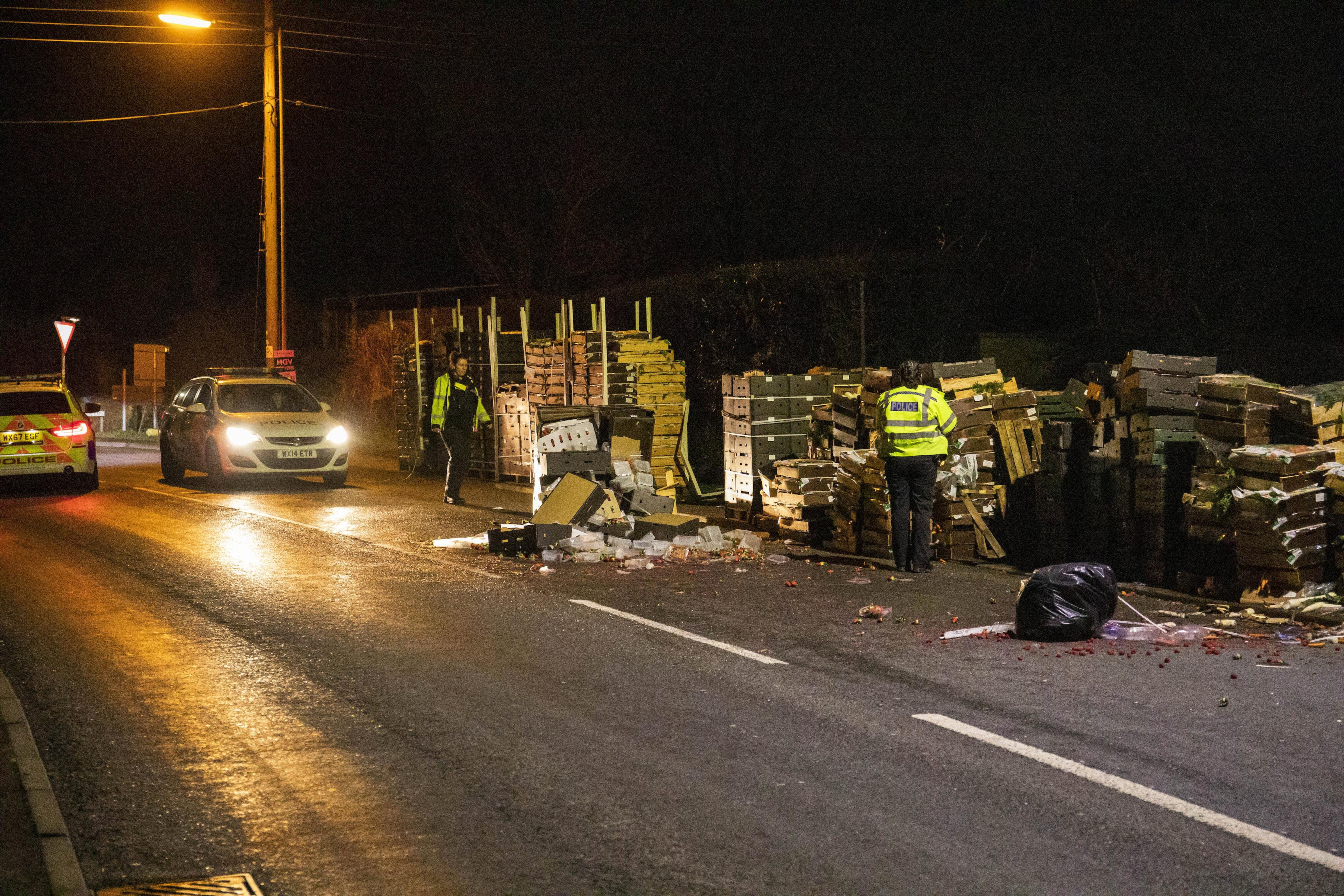 Wooden pallets full of fruit and vegetables are left strewn across the A38 into North Petherton after a member of public reported seeing several people coming out of a lorry on the road resulting in a police investigation and numerous arrests on suspicion of immigration offences. Somerset. 16 January 2020. See SWNS story SWBRlorry