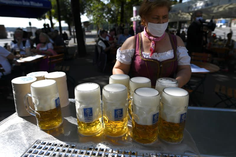 FILE PHOTO: Server carries mugs during barrel tapping at beer garden near Theresienwiese, Munich