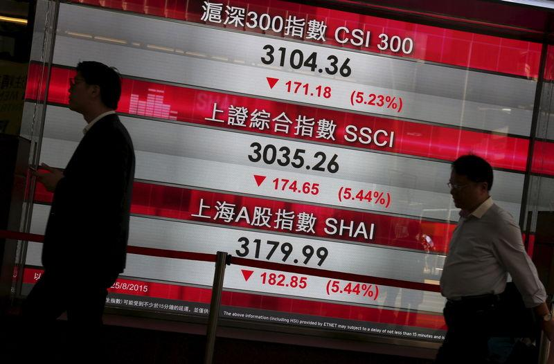 Passers-by walk past a panel displaying falling China stock indexes, at the financial Central district in Hong Kong