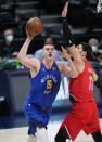 Denver Nuggets center Nikola Jokic (15) goes up for a shot against Portland Trail Blazers center Enes Kanter (11) during the first half of Game 1 of a first-round NBA basketball playoff series Saturday, May 22, 2021, in Denver. (AP Photo/Jack Dempsey)
