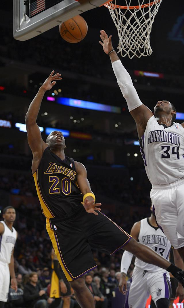 Los Angeles Lakers guard Jodie Meeks, left, puts up a shot as Sacramento Kings forward Jason Thompson defends during the first half of an NBA basketball game, Friday, Feb. 28, 2014, in Los Angeles. (AP Photo/Mark J. Terrill)