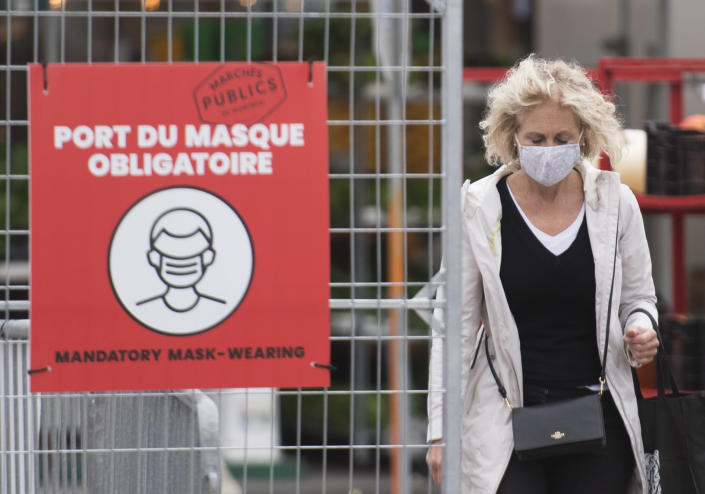A woman wears a face mask as she walks through a market in Montreal, which has been Canada's epicentre throughout the COVID-19 pandemic. (Credit: The Canadian Press/Graham Hughes)