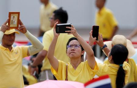 A woman takes pictures outside the balcony of Suddhaisavarya Prasad Hall at the Grand Palace where of King Maha Vajiralongkorn will grant a public audience to receive the good wishes of the people in Bangkok, Thailand May 6, 2019. REUTERS/Jorge Silva