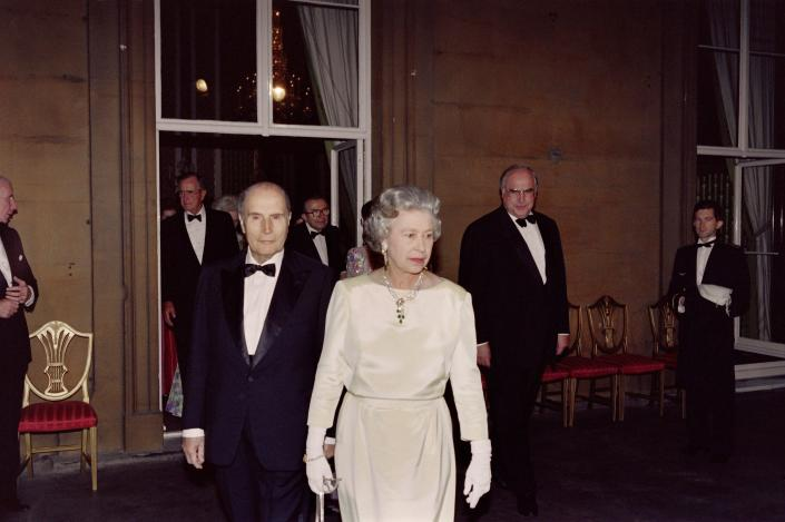 Britain's Queen Elizabeth II leads French President François Mitterrand (L), German Chancellor Helmut Kohl (R) and other participants onto a balcony of Buckingham Palace following a banquet during the London 17th G7 Summit on July 16, 1991. (Photo by JEAN-LOUP GAUTREAU / AFP)        (Photo credit should read JEAN-LOUP GAUTREAU/AFP via Getty Images)