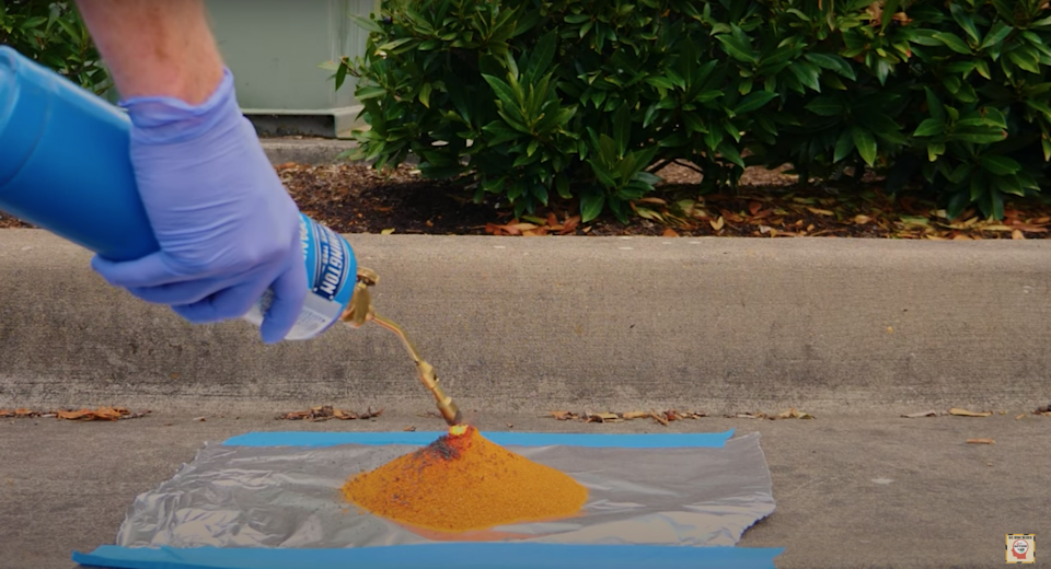 A gloved hand using a handheld torch to light a mound of ammonium dichromate outside.