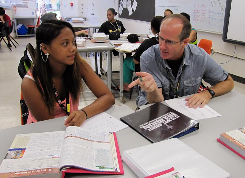 Dennis Tynan, right, talks to 9th grader Chyda Iokua during a 9th grade social studies class at Nakakuli High and Intermediate School in Waianae, Hawaii on Friday, Aug. 9, 2013. Hawaii, the only state with a single, statewide district, has long had to turn to the mainland because local teacher education programs can't produce enough graduates to fill classrooms across the islands, especially in remote schools. Getting the newcomers to stay is difficult, as they face culture shock, a high cost of living and a vast ocean separating them from their families. (AP Photo/Jennifer Sinco Kelleher)