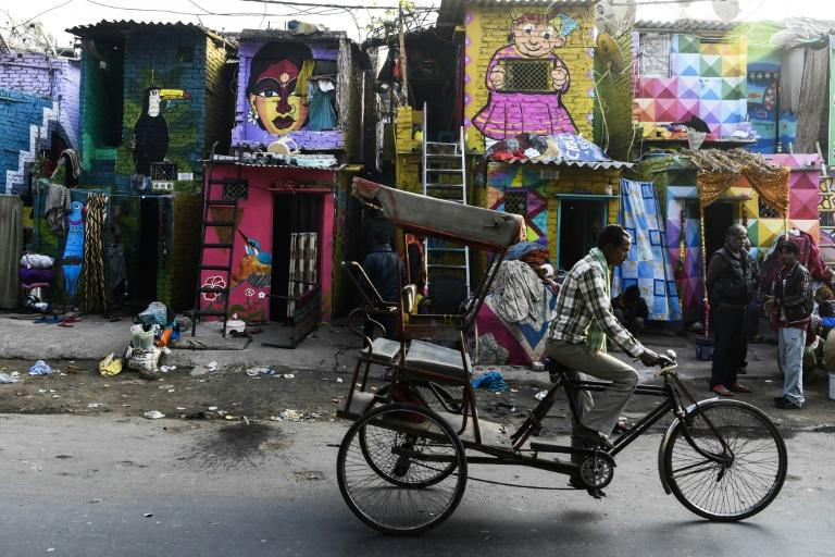 A rickshaw driver cycles past homes adorned with murals by the 'Delhi Street Art' group