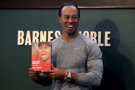 """Golfer Tiger Woods poses with a copy of his new book """"The 1997 Masters: My Story"""" at a book signing event at a Barnes & Noble store in New York"""
