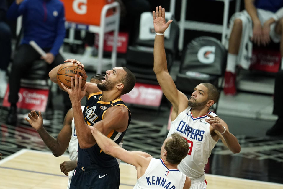 Utah Jazz center Rudy Gobert, left, drives to the basket against the Los Angeles Clippers during the first half of an NBA preseason basketball game Thursday, Dec. 17, 2020, in Los Angeles. (AP Photo/Marcio Jose Sanchez)