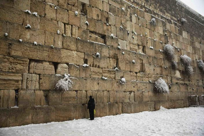 A man prays in the snow at the Western Wall, Judaism's holiest prayer site, in Jerusalem's Old City February 20, 2015. Snow covered Jerusalem and mountainous areas of Israel early Friday morning and the education ministry closed schools for the day. (REUTERS/Ronen Zvulun)