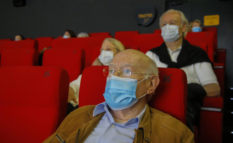 People wear protective masks as they wait for the screening of a movie in Paris, Monday, June 22, 2020. (AP Photo/Michel Euler)