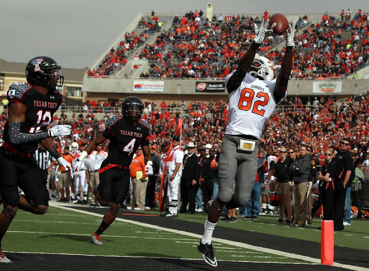 LUBBOCK, TX - NOVEMBER 12:  Isaiah Anderson #82 of the Oklahoma State Cowboys makes a touchdown pass against D.J. Johnson #12 of the Texas Tech Red Raiders at Jones AT&T Stadium on November 12, 2011 in Lubbock, Texas.  (Photo by Ronald Martinez/Getty Images)