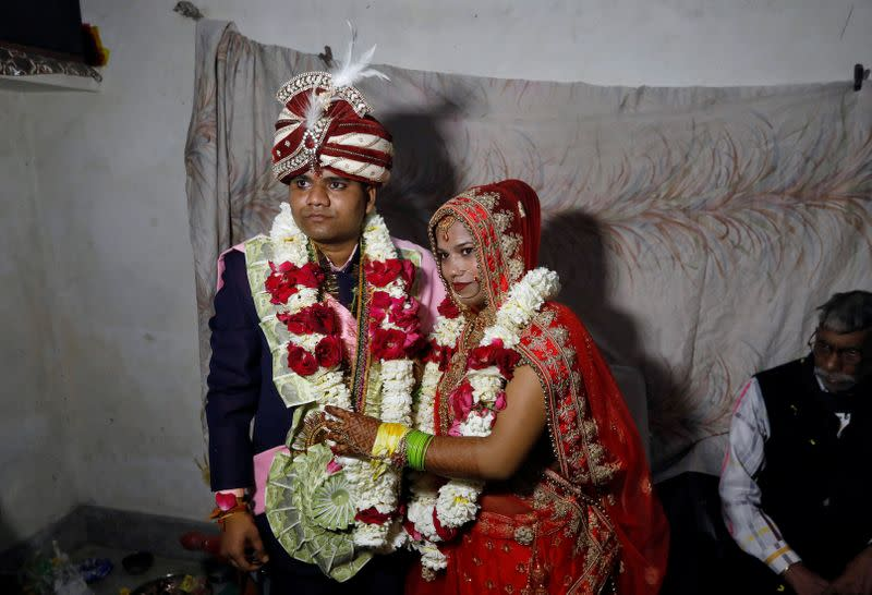 Savitri Prasad and her husband Gulshan pose after taking their wedding vows inside Savitri's parents' house in a riot affected area following clashes between people demonstrating for and against a new citizenship law in New Delhi