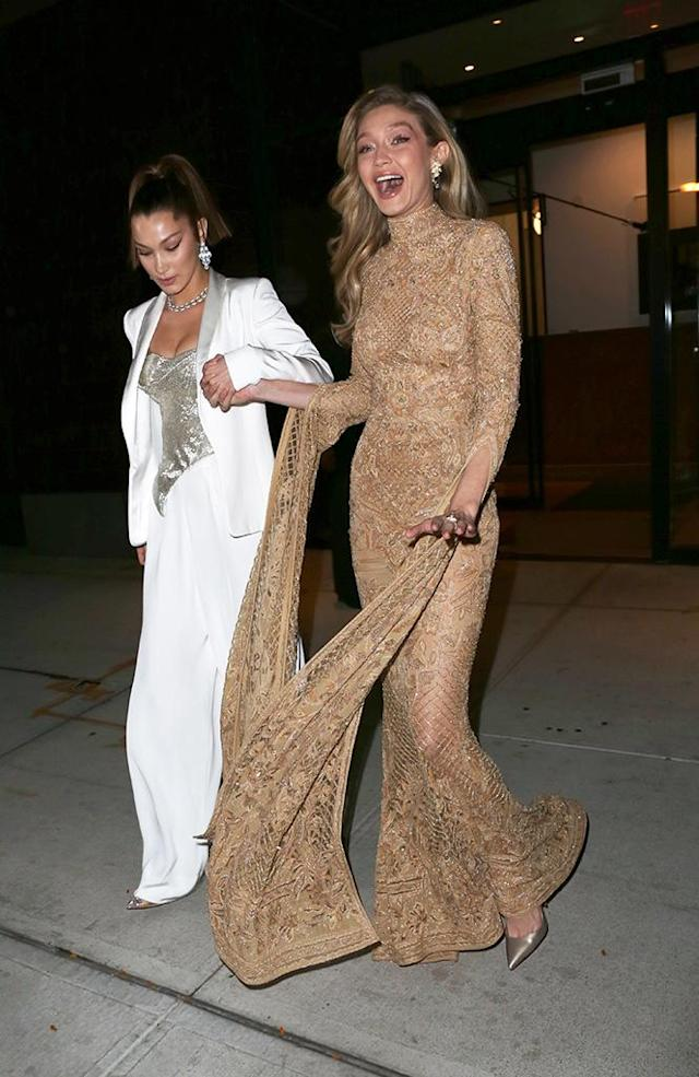 """<p>Bella saved the day when she rescued her sister from <a href=""""https://www.yahoo.com/lifestyle/gigi-hadid-almost-totally-wiped-couture-gown-153536497.html"""" data-ylk=""""slk:a near fall;outcm:mb_qualified_link;_E:mb_qualified_link"""" class=""""link rapid-noclick-resp newsroom-embed-article"""">a near fall</a> when Gigi got caught up in her gold gown on Monday in NYC. No worries, though: Zayn Malik's girlfriend of two years took it all in stride and laughed it off, quickly recovering and getting back to her runway walk. (Photo: Richard Buxo/Splash News) </p>"""