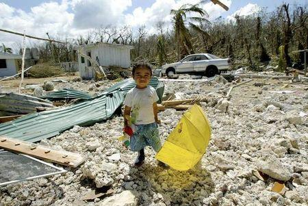 A CHILD STANDS AMONG RUINS FOLLOWING CYCLONE HETA ON THE PACIFIC ISLAND OF NIUE.