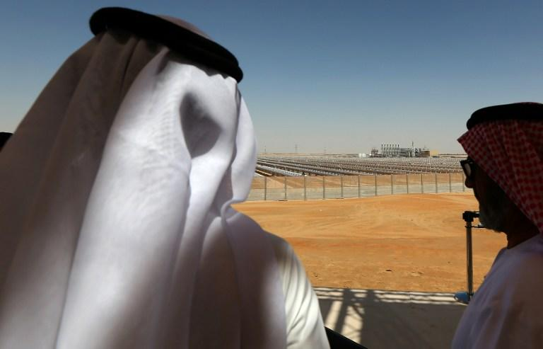 Emarati men stand on a balcony overlooking the Shams 1, Concentrated Solar power (CSP) plant, in al-Gharibiyah district on the outskirts of Abu Dhabi, on March 17, 2013 during the inauguration of the facility. Oil-rich Abu Dhabi officially opened the world's largest Concentrated Solar Power (CSP) plant, which cost $600 million to build and will provide electricity to 20,000 homes. AFP PHOTO/MARWAN NAAMANI