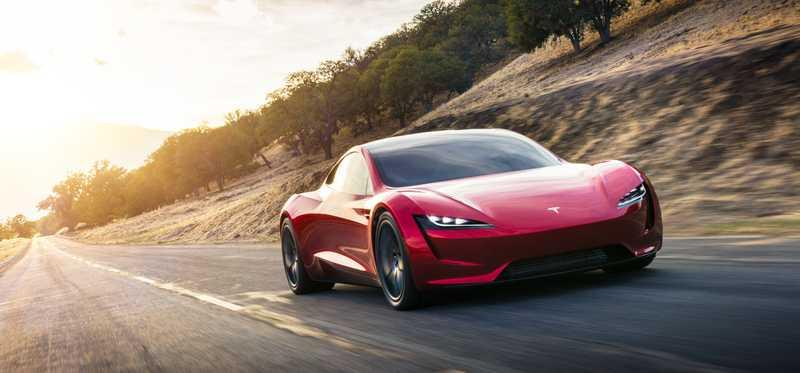 A red Tesla Roadster on the road.