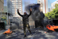 A man shouts slogans in front of burning tires and garbage containers set on fire to block a main road during a protest against the increase in prices of consumer goods and the crash of the local currency, in Beirut, Lebanon, Tuesday, March 16, 2021. Scattered protests broke out on Tuesday in different parts of the country after the Lebanese pound hit a new record low against the dollar on the black market. (AP Photo/Hussein Malla)
