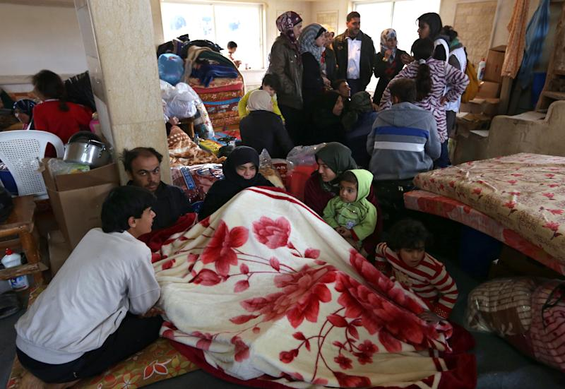 Syrian refugees gather inside a restaurant after they fled into the eastern Lebanese border town of Arsal, Lebanon, Monday, Nov. 18, 2013. Thousands of Syrians have fled to Lebanon over the past days as government forces attack the western town of Qarah near the border with Lebanon. (AP Photo/Bilal Hussein)