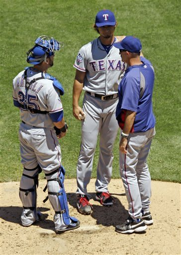 Texas Rangers starting pitcher Yu Darvish, center, gets a visit on the mound from pitching coach Mike Maddux, right, and catcher Mike Napoli after loading the bases against the Oakland Athletics during the first inning of a baseball game Thursday, June 7, 2012, in Oakland, Calif. (AP Photo/Marcio Jose Sanchez)