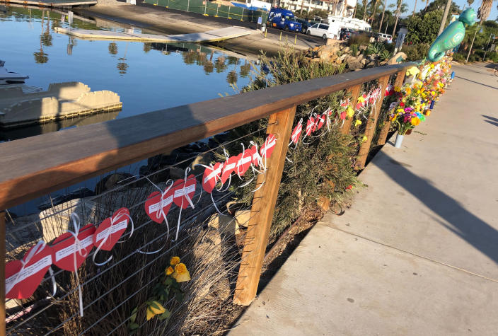 A row of hearts, each with the name of a victim, adorn a growing memorial to those who died aboard the dive boat Conception, seen early Friday morning, Sept. 6, 2019 at the harbor in Santa Barbara, Calif. The Sept. 2 fire took the lives of 34 people on the ship off Santa Cruz Island off the Southern California coast near Santa Barbara (AP Photo/Stefanie Dazio)