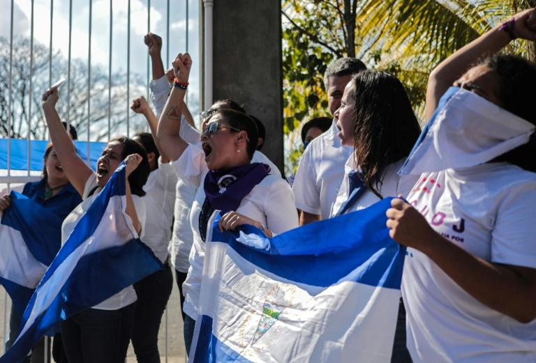 Opposition demonstrators shout slogans as they wave Nicaraguan flags during a protest outside the Divina Misericordia church in Managua