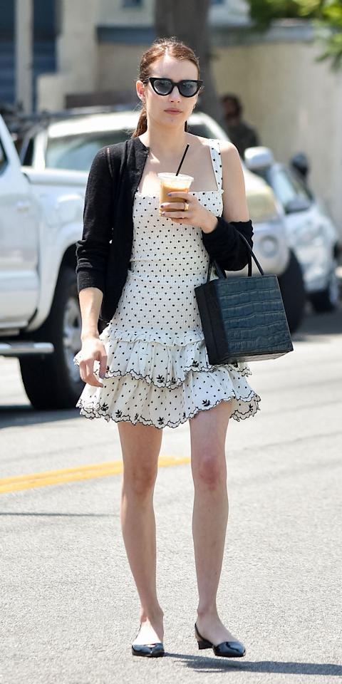 "<p>Emma Roberts enjoyed an iced coffee while wearing a Wayf polka-dot dress ($103; <a href=""https://amzn.to/32ZuZC2"" target=""_blank"">amazon.com</a>), black cardigan, croc bag, and Aera slingback shoes ($345; <a href=""https://aeranewyork.com/collections/flat-shoes/products/458104f-audrey-black-patent-effect"" target=""_blank"">aeranewyork.com</a>).</p>"