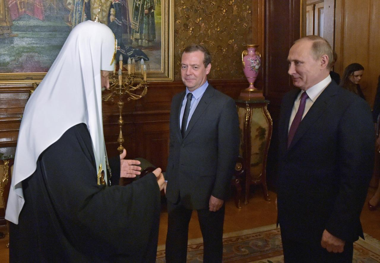 Russian President Vladimir Putin, right, and Prime Minister Dmitry Medvedev, center, congratulate Russian Orthodox Patriarch Kirill on his name day in Moscow, Russia, Wednesday, May 24, 2017. (Alexei Nikolsky/Sputnik, Kremlin Pool Photo via AP)