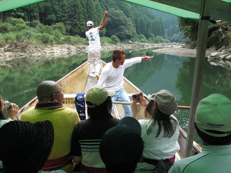 This August 2012 photo shows an oarsman piloting an excursion boat down the Hozu River, just outside Kyoto, Japan, as he points out sights to his passengers. The two-hour ride down the river offers the chance to spot wildlife while threading rocks and rapids, and is an especially appealing outing for a trip with children. (AP Photo/Adam Geller)