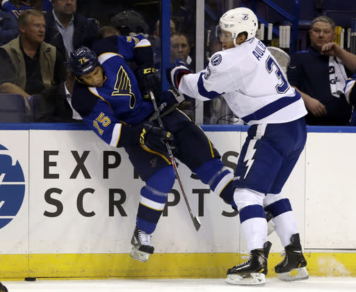 Tampa Bay Lightning's Keith Aulie, right, pushes St. Louis Blues' Ryan Reaves off the puck during the first period of a preseason NHL hockey game Friday, Sept. 20, 2013, in St. Louis. (AP Photo/Jeff Roberson)