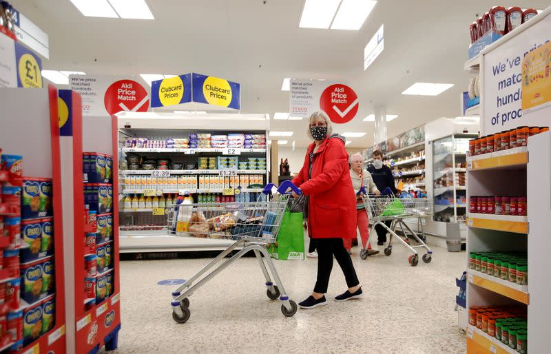 FILE PHOTO: A woman wearing a face mask pushes a shopping cart at a Tesco supermarket in Hatfield