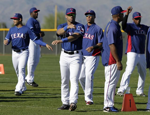 Seattle Seahawks quarterback Russell Wilson, center, runs through morning stretches with the Texas Rangers during spring training baseball practice, Monday, March 3, 2014, in Surprise, Ariz. (AP Photo/Tony Gutierrez)