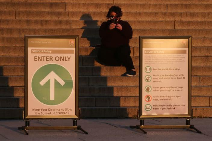 A woman in a mask takes a picture of the sunrise from the steps at the Lincoln Memorial during the coronavirus disease (COVID-19) outbreak, where normally thousands of Christians would gather for worship at Easter sunrise, in Washington