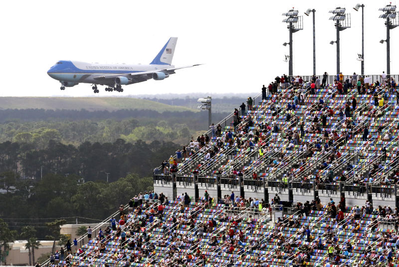 Race fans watch from the grandstands as Air Force One circles the Daytona International Speedway as President Donald Trump makes his arrival to attend the NASCAR Daytona 500 auto race at Daytona International Speedway, Sunday, Feb. 16, 2020, in Daytona Beach, Fla. (AP Photo/Jim Topper)