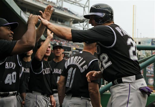 Colorado Rockies Jordan Pacheco, right, reacts with teammates after scoring on a wild pitch during the ninth inning of a baseball game against the Washington Nationals, Sunday, July 8, 2012, in Washington. The Rockies won 4-3. (AP Photo/Alex Brandon)