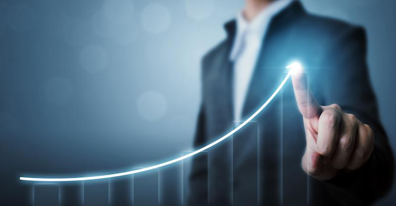 A person in a business suit drawing an upward trending curve with his/her index finger.
