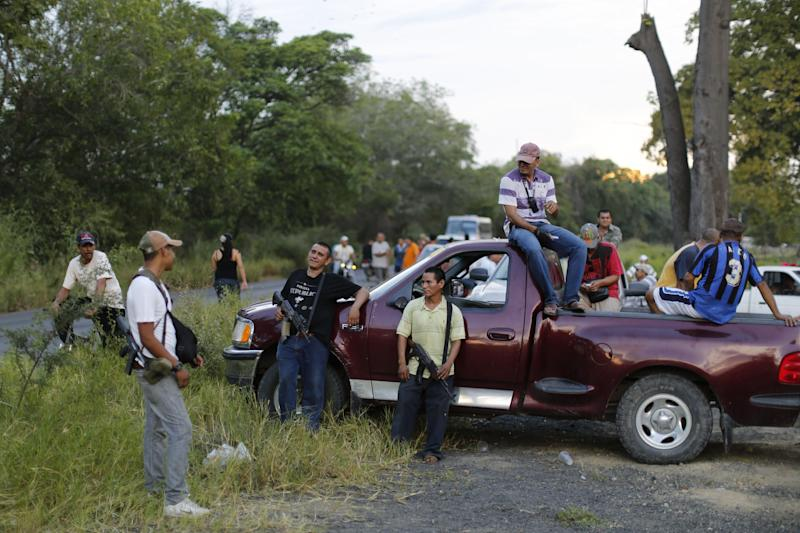 In this Nov. 5 photo, villagers who are members of the local self-defense group gather to block a road in response to soldiers allegedly confiscating a handful of their weapons in Las Colonias, Mexico. The group says that soldiers confiscated a few of their weapons and that their leaders were negotiating with the army to get them back. The self-defense groups started small with just a few dozen civilians from a couple of communities_lime pickers, ranchers and business owners who began patrolling the streets, setting up roadblocks and ambushing the Knights Templar as the drug men roamed with their heavy artillery and SUVs. (AP Photo/Dario Lopez-Mills)