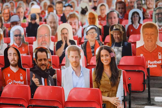 Harry and Meghan the Duke and Duchess of Sussex amid cardboard fans profile pictures. (Getty Images)