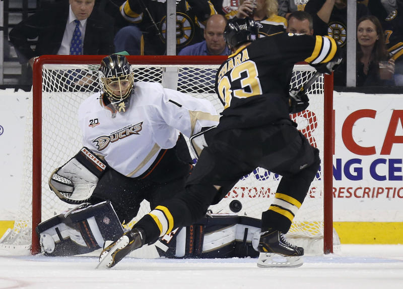 Anaheim Ducks' Jonas Hiller, left, of Switzerland, blocks the shot by Boston Bruins' Zdeno Chara, of Slovakia, in the first period of an NHL hockey game in Boston, Thursday, Oct. 31, 2013. (AP Photo/Michael Dwyer)