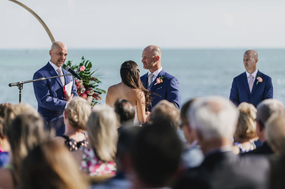 Associated Press sportswriter Larry Lage, left, officiates the wedding of Ryan Rutledge and Natalie LaRocca at the Postcard Inn Beach Resort and Marina in Islamorada, Fla. on March 27, 2021. (Photo courtesy of Lukas Guillaume via AP)