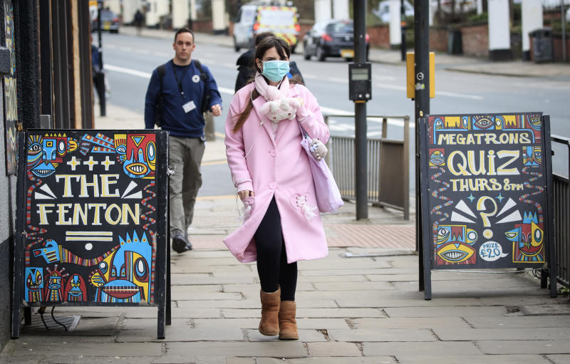 A woman wearing a face mask walks past pub signs in Leeds, West Yorkshire, the day after Prime Minister Boris Johnson called on people to stay away from pubs, clubs and theatres, work from home if possible and avoid all non-essential contacts and travel in order to reduce the impact of the coronavirus pandemic.