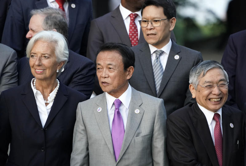 Japan's Finance Minister Taro Aso, center, stands with IMF Managing Director Christine Lagarde, left, and Bank of Japan Governor Haruhiko Kuroda, right, before a family photo of the G20 finance ministers and central bank governors meeting Saturday, June 8, 2019, in Fukuoka, Japan. The G20 finance ministers and central bank governors meeting is taking place in Fukuoka June 8-9. (Franck Robichon/Pool Photo via AP)