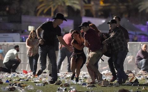 <span>People carry an injured person at the Route 91 Harvest country music festival</span> <span>Credit: David Becker/Getty </span>