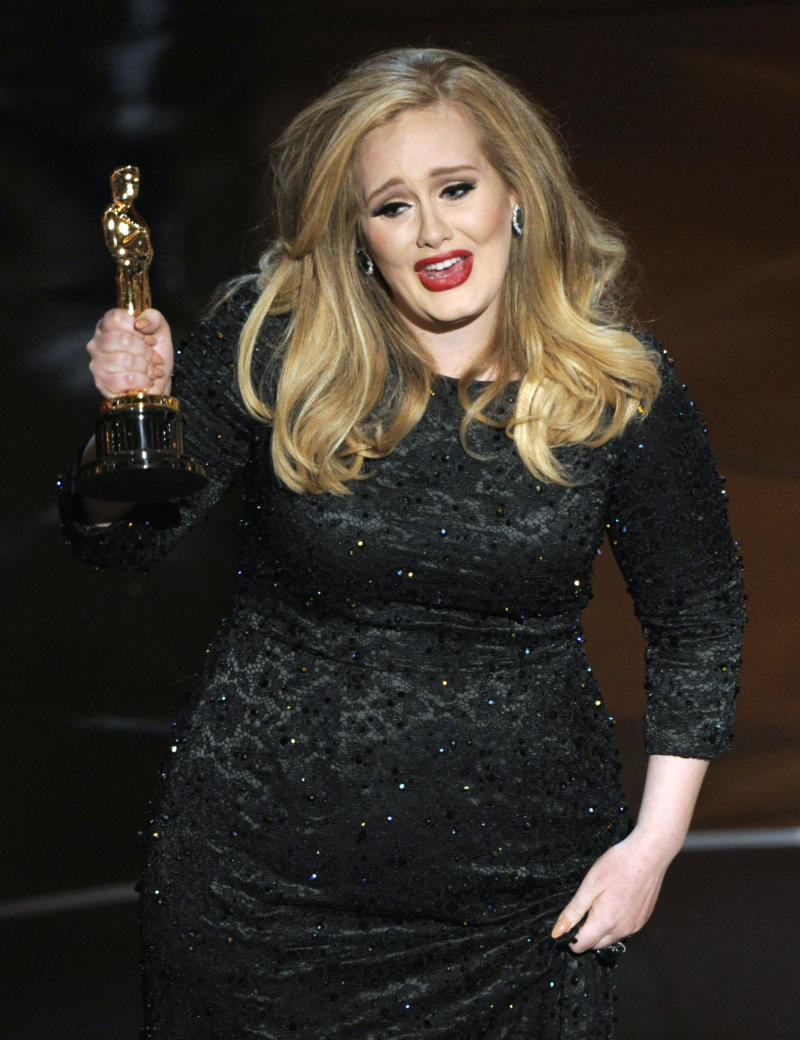 """Singer Adele accepts the award for best music - original song for """"Skyfall,"""" from the film """"Skyfall,"""" during the Oscars at the Dolby Theatre on Sunday Feb. 24, 2013, in Los Angeles.  (Photo by Chris Pizzello/Invision/AP)"""