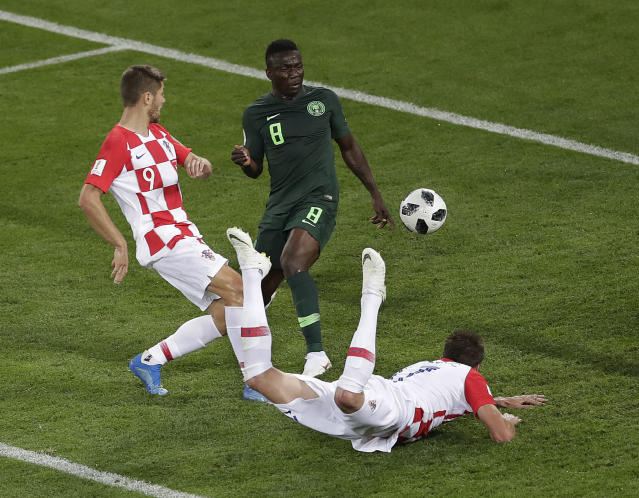 Croatia's Mario Mandzukic, right, heads the ball to make Nigeria's Oghenekaro Etebo score an own goal ti give Croatia a 1-0 lead during the group D match between Croatia and Nigeria at the 2018 soccer World Cup in the Kaliningrad Stadium in Kaliningrad, Russia, Saturday, June 16, 2018. (AP Photo/Michael Sohn)