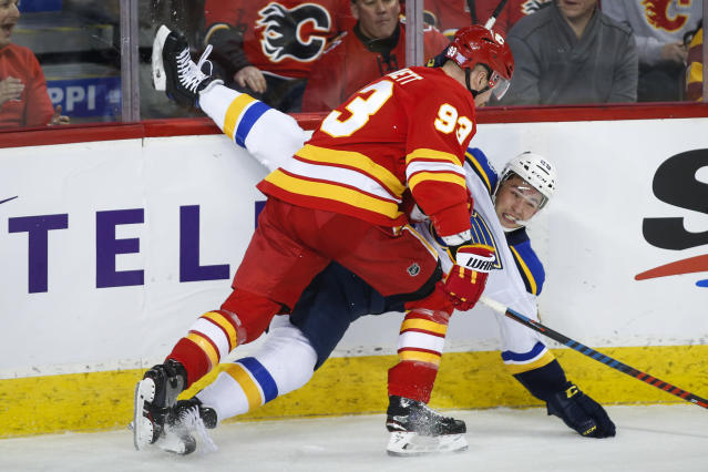 St. Louis Blues' Vince Dunn, right, is checked by Calgary Flames' Sam Bennett during the first period of an NHL hockey game in Calgary, Saturday, Nov. 9, 2019. (Jeff McIntosh/The Canadian Press via AP)